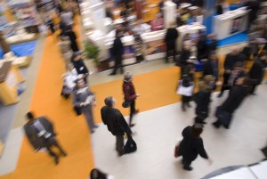 Visitors passing by stands at exhibition